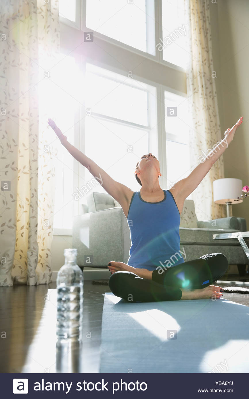 Mature woman with arms raised performing yoga against window at home - Stock Image