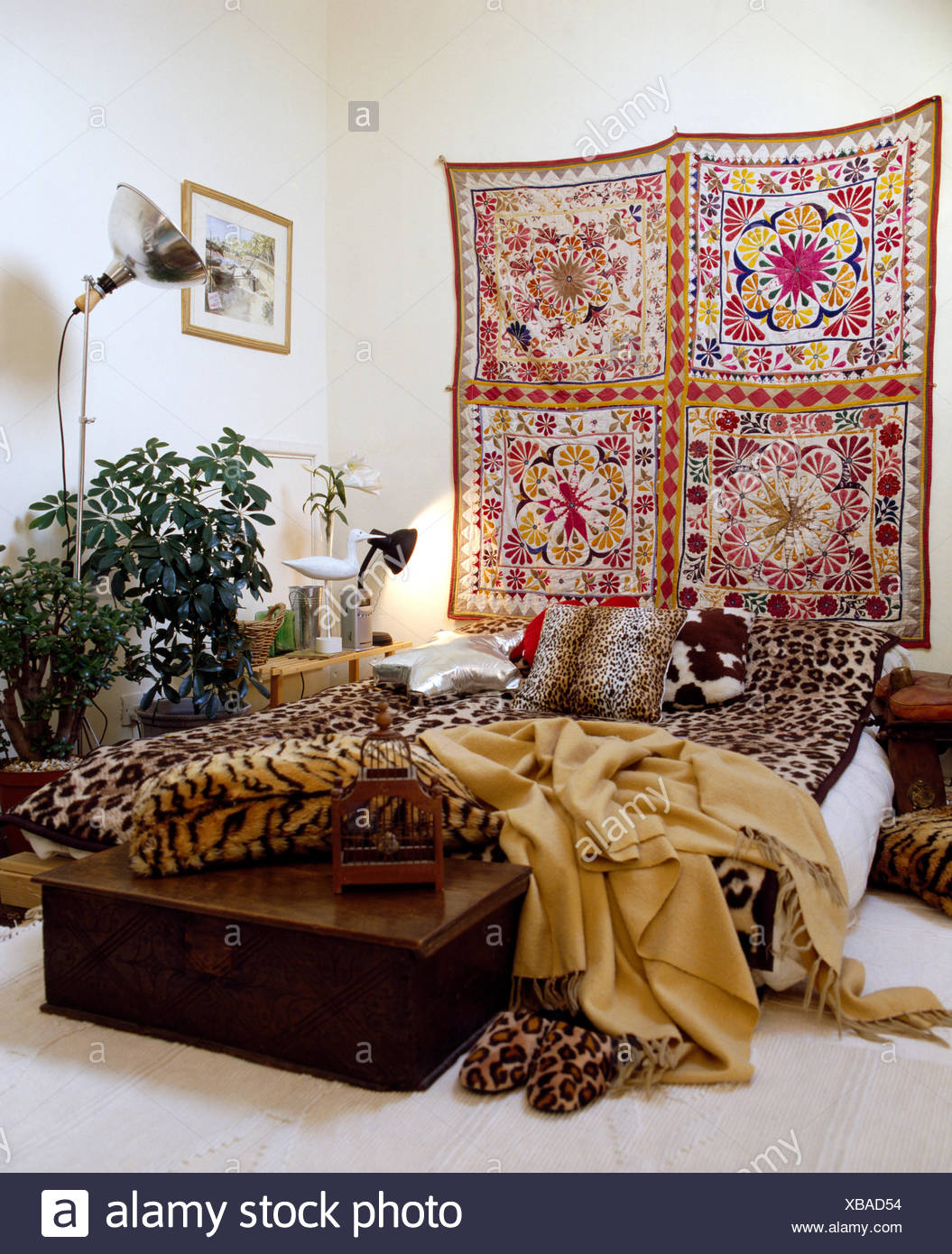 bedroom with large floral cotton wall hanging above bed with faux animal skin cushions and throws - Throws Bedroom