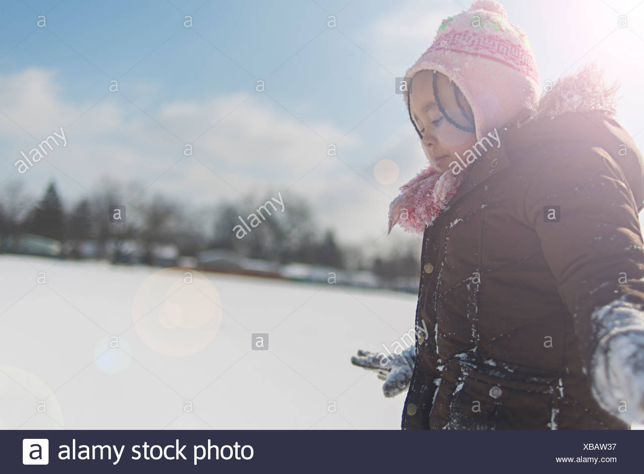 Young girl cautiously trying to walk in snow covered field - Stock Image