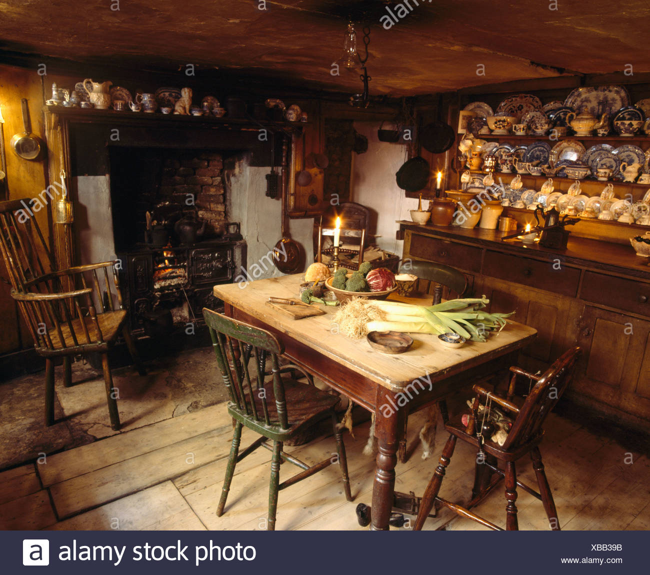 Old pine table and dresser in old-fashioned kitchen dining room with antique  Windsor chair beside fireplace with lighted fire - Old Pine Table And Dresser In Old-fashioned Kitchen Dining Room With