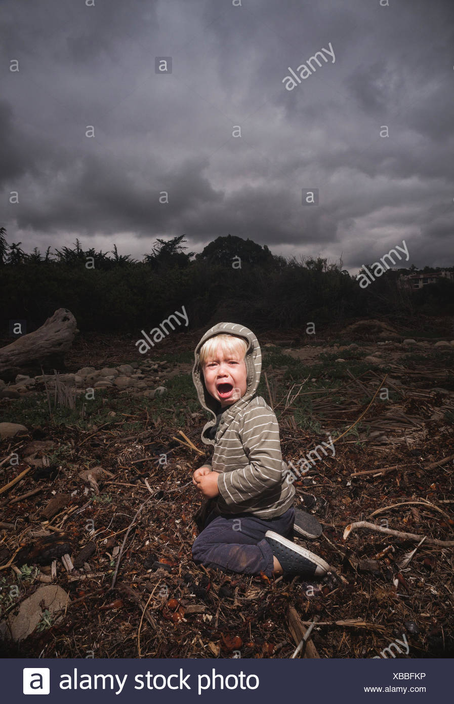 Young boy kneeling on ground crying against stormy sky - Stock Image
