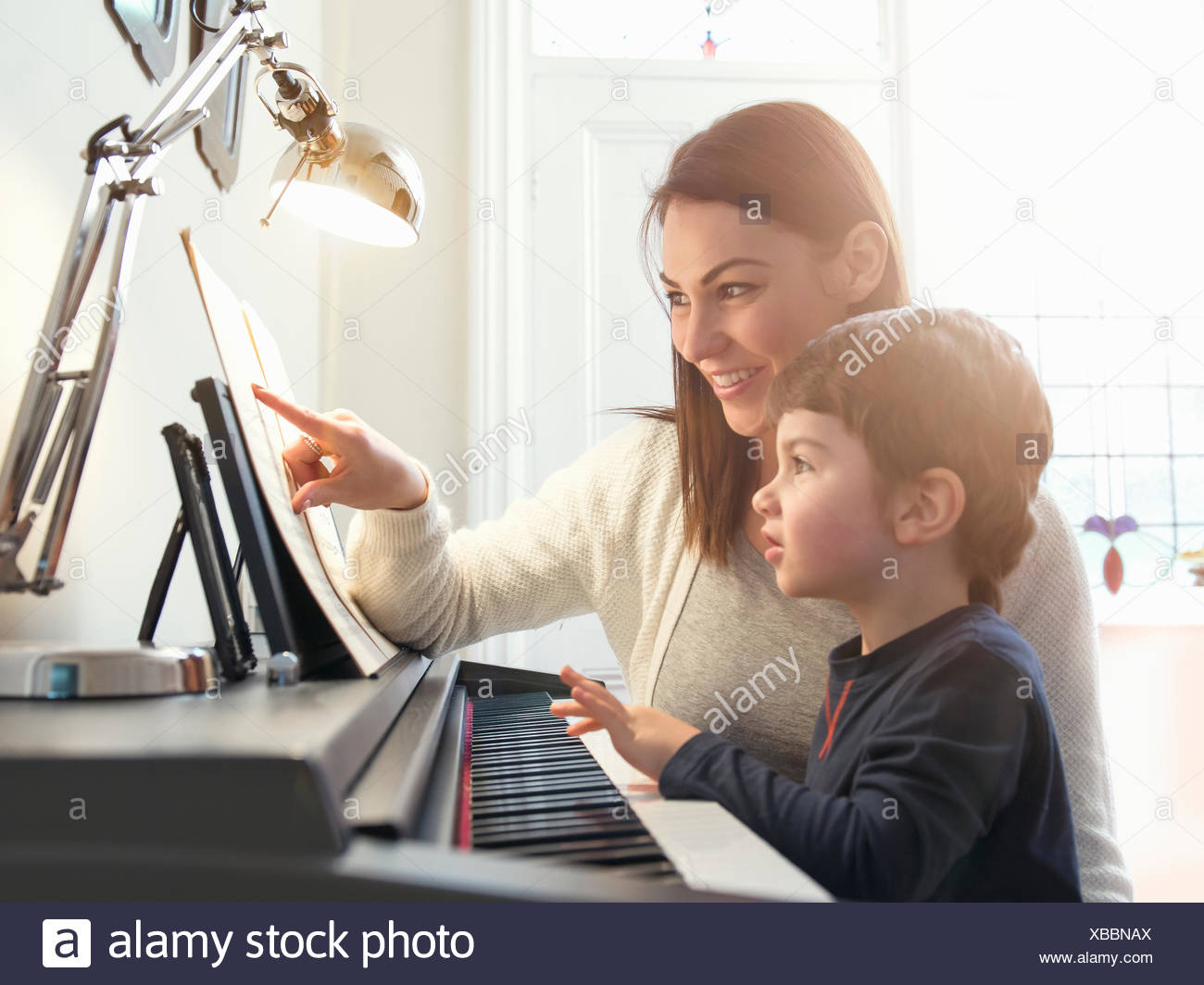 Mother pointing at sheet music to teach son to play piano at home - Stock Image