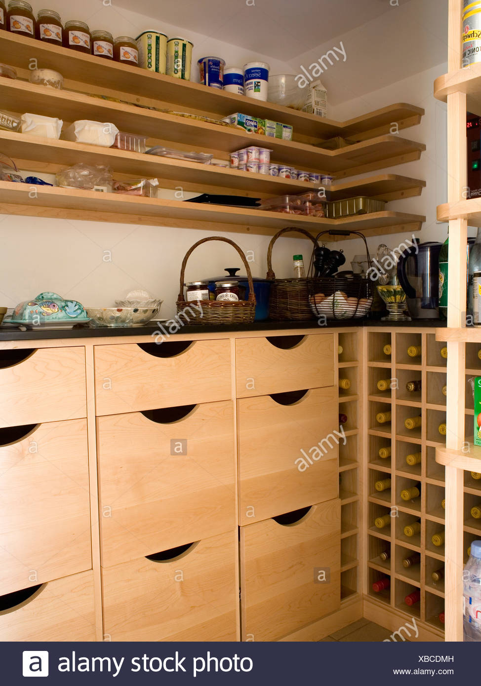 Simple Wooden Shelving Above Pale Wood Storage Drawers In Corner Of  Economy Style Country Kitchen With Fitted Wine Rack