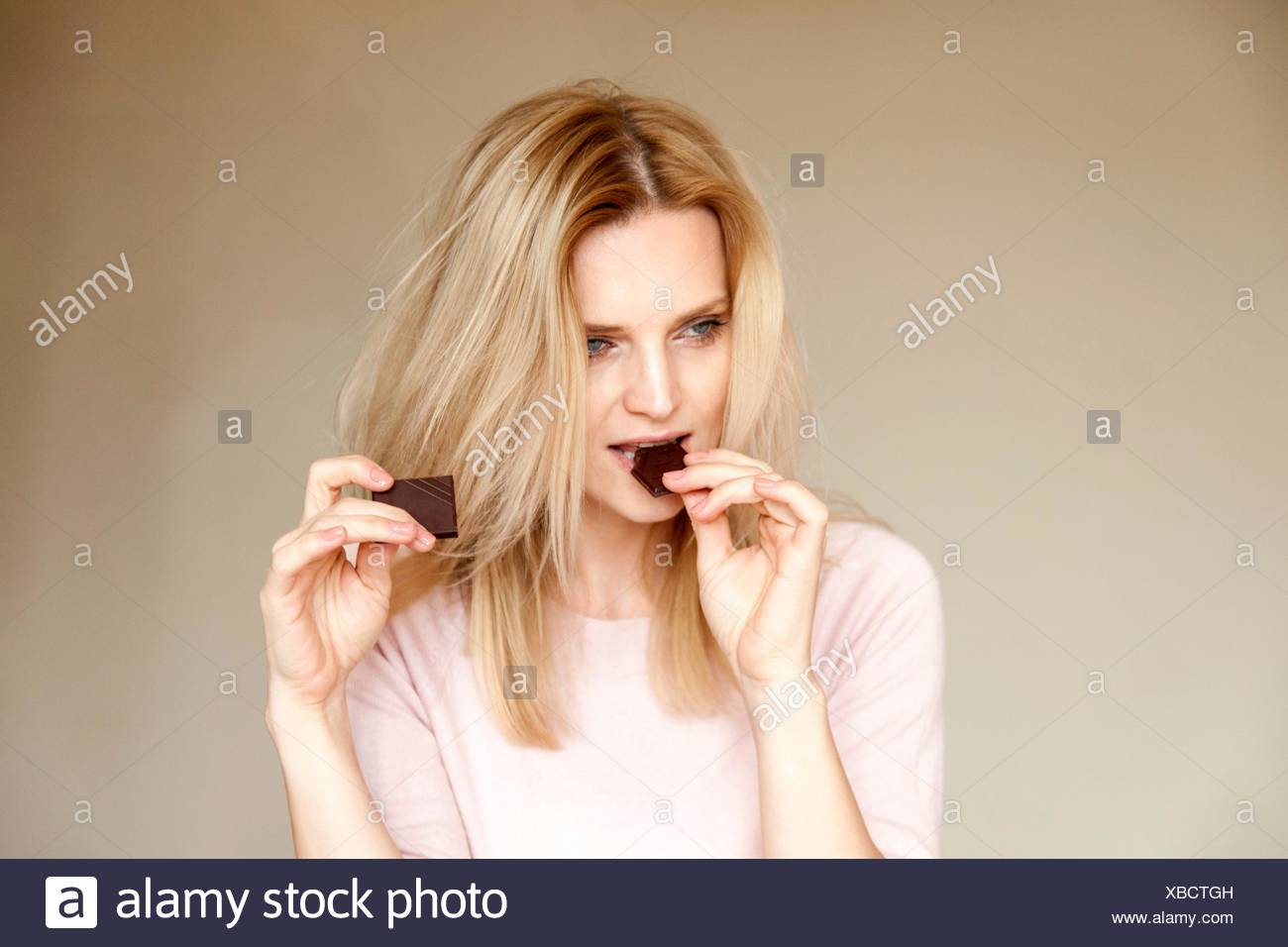 Portrait of beautiful woman with long blond hair eating chocolate bar - Stock Image
