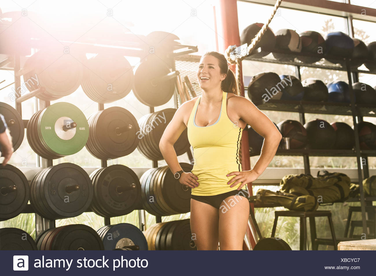 Happy bodybuilder standing in front of gym apparatus - Stock Image