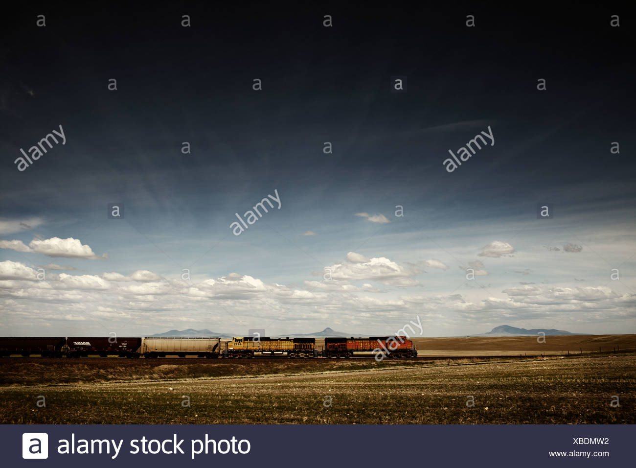 A train rolls across the American prairie south of the Sweetgrass Hills in Montana. - Stock Image