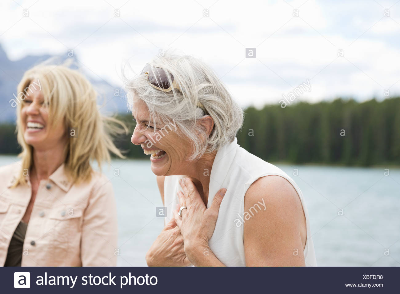 Mature female friends laughing outdoors - Stock Image