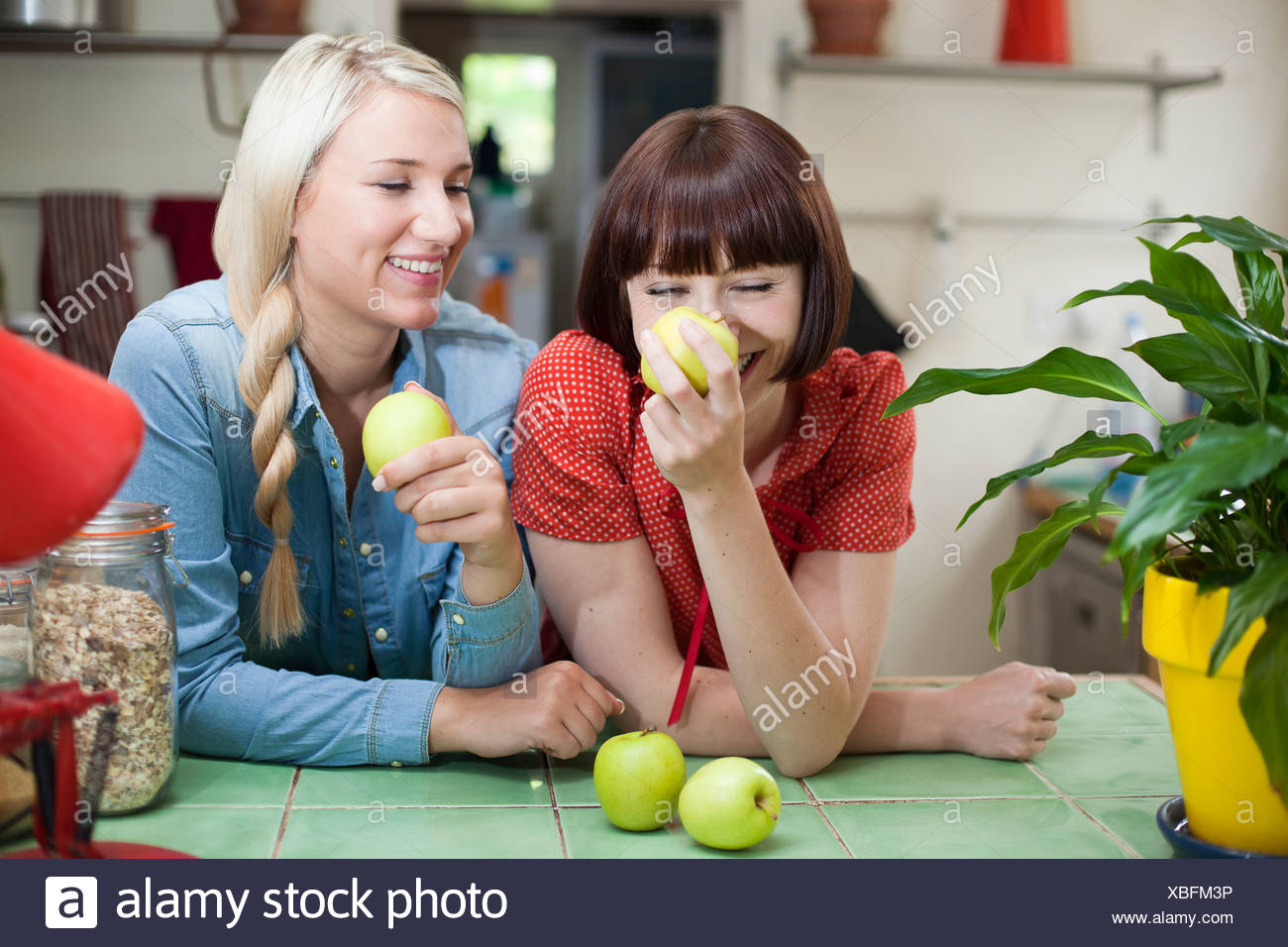 Female friends in kitchen with apples - Stock Image