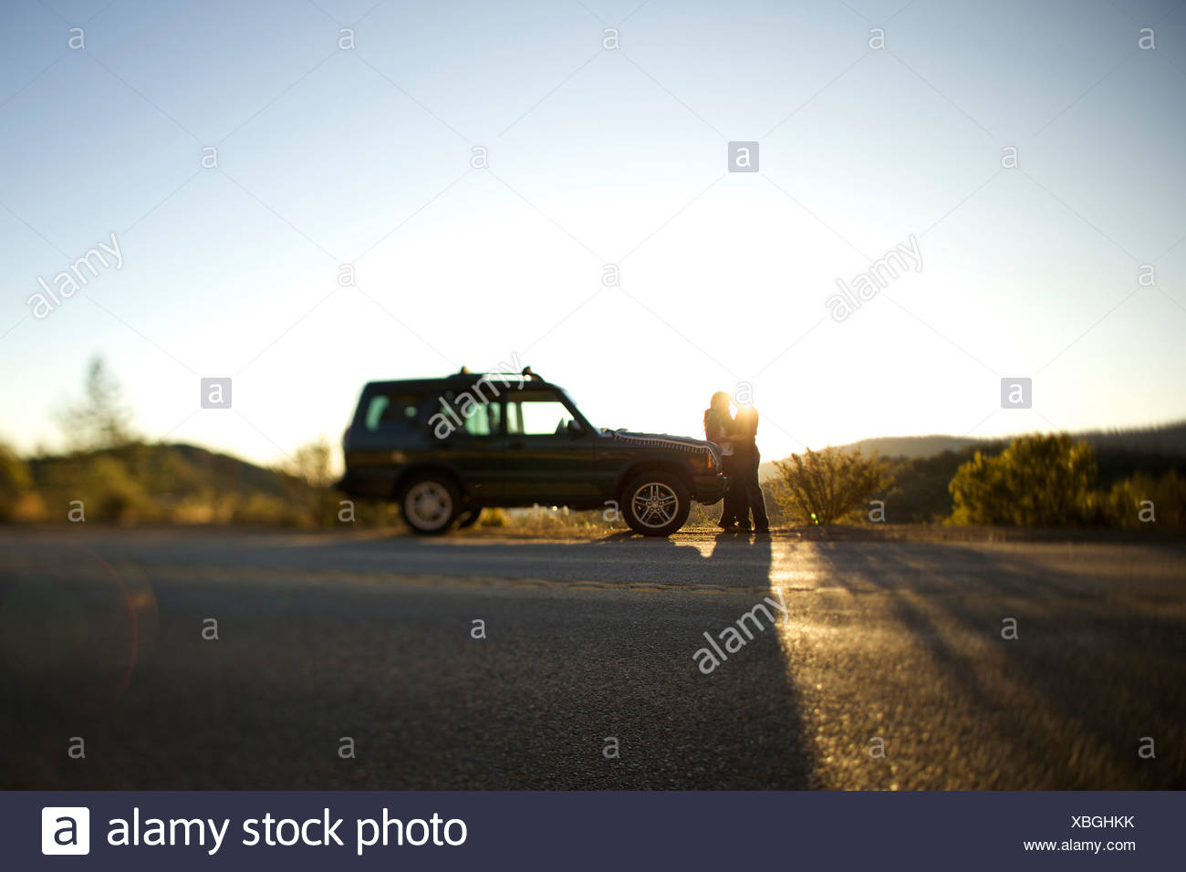 Couple park their car on the side of the road  to watch the sunset. - Stock Image