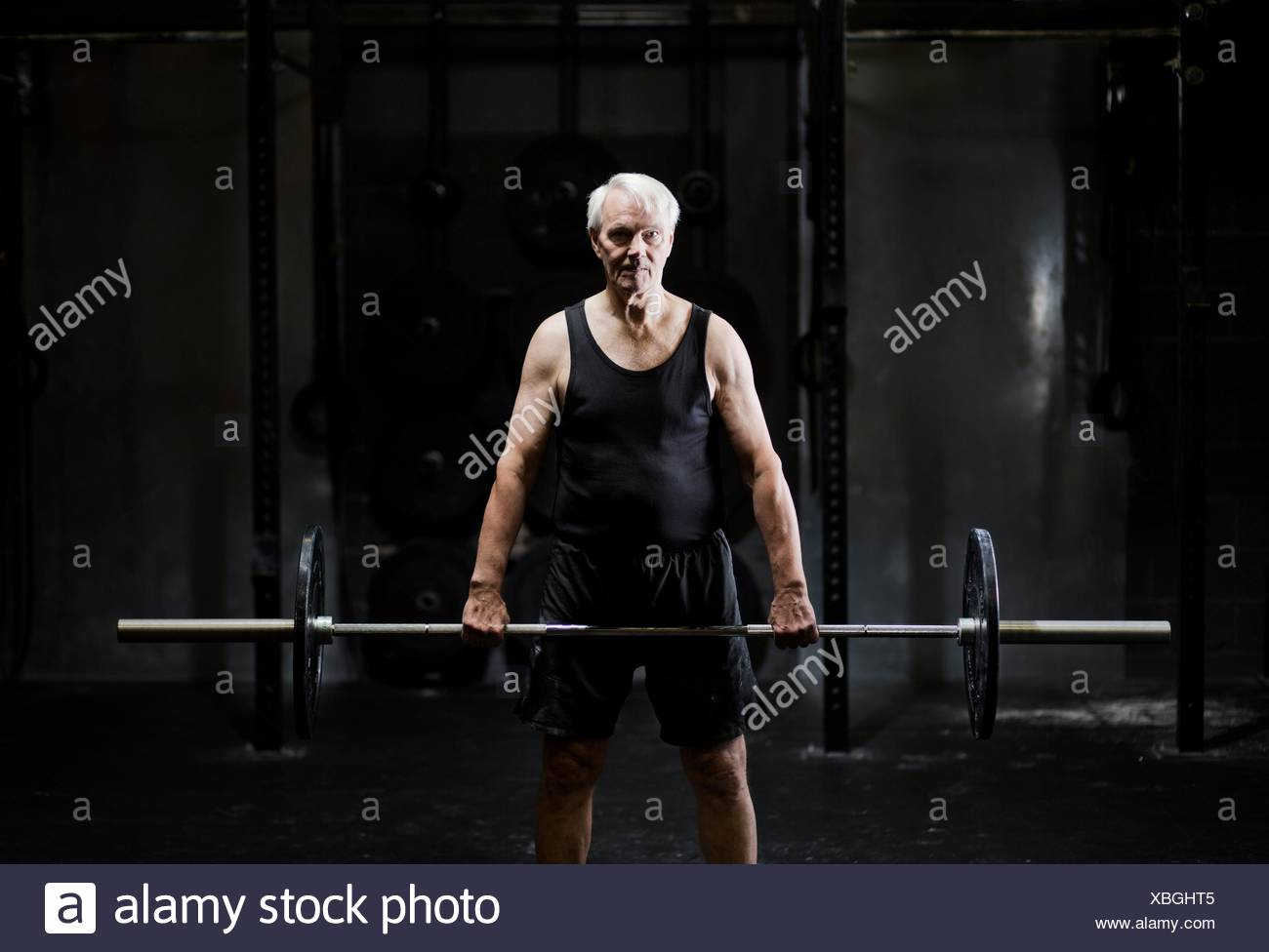 Senior man weightlifting barbell in dark gym - Stock Image