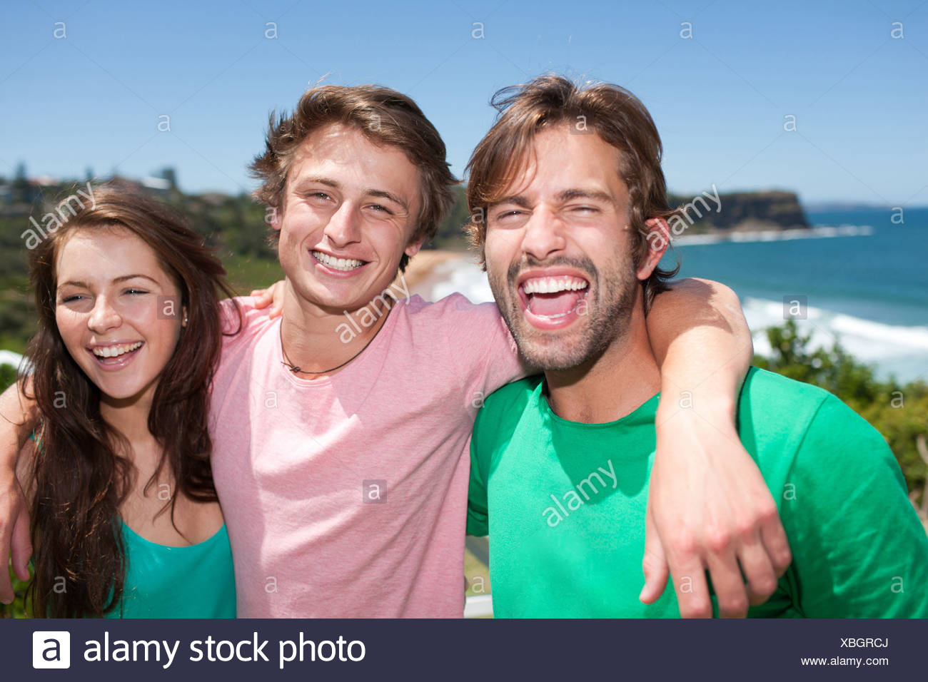 Friends hugging and smiling - Stock Image