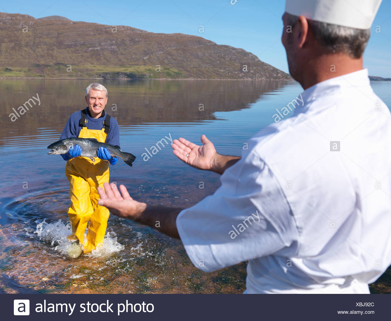 Fisherman and chef with salmon by lake - Stock Image