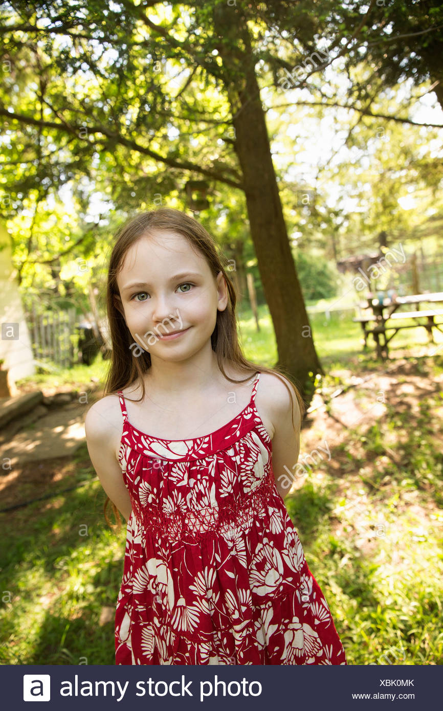 A young girl in a red floral summer dress in the shade of trees. - Stock Image