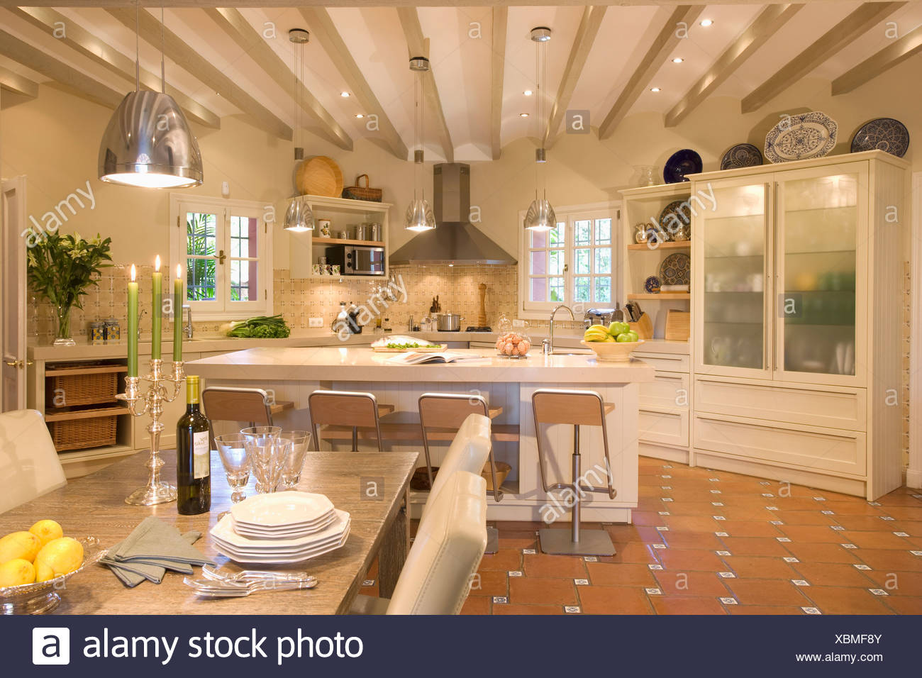 Large Openplan Kitchen Dining Room With Glass Fronted Cupboard Breakfast Bar And Pendant Light Above Table