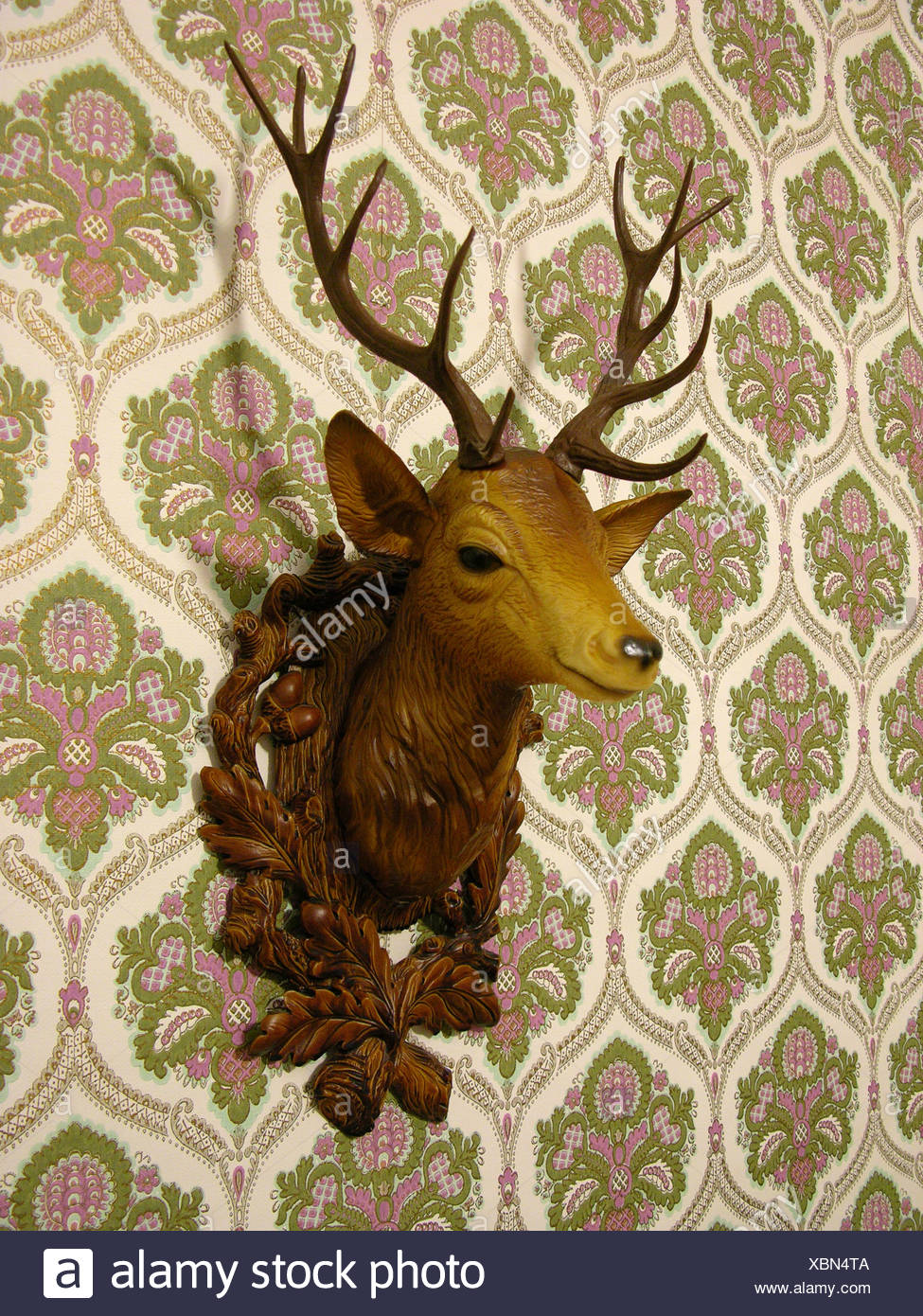 Plastic deer head on an old-fashioned wallpaper - Stock Image