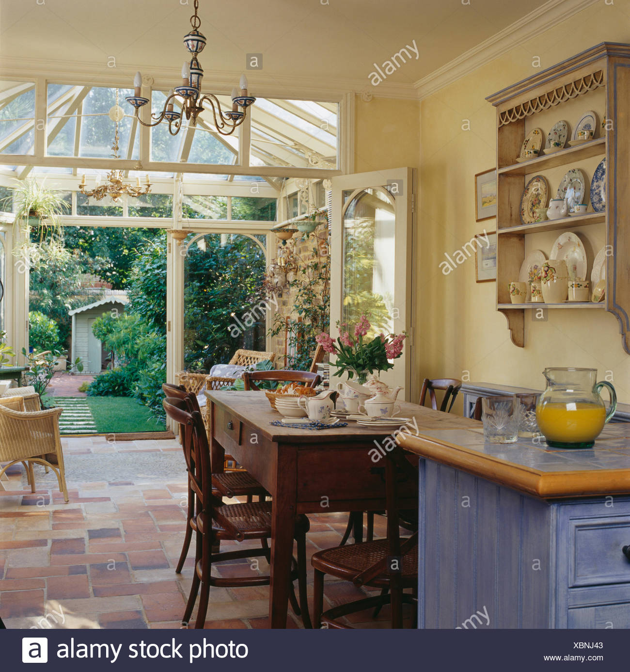 Simple Wooden Table And Chairs In Country Kitchen Dining Room With Conservatory Extension Doors Open