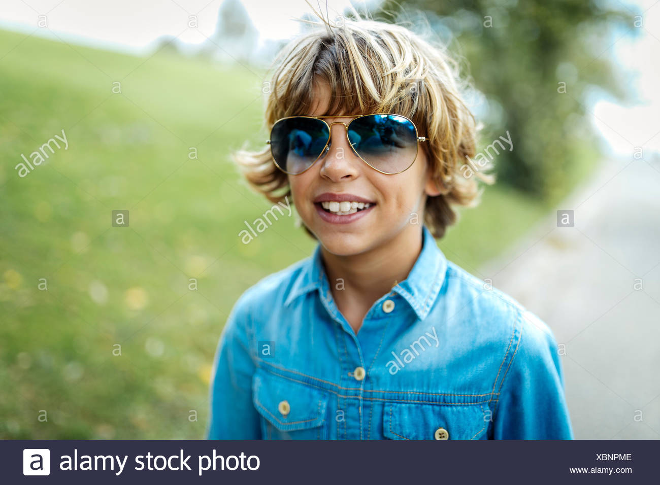 Portrait of blond boy wearing blue coloured sunglasses and denim shirt - Stock Image