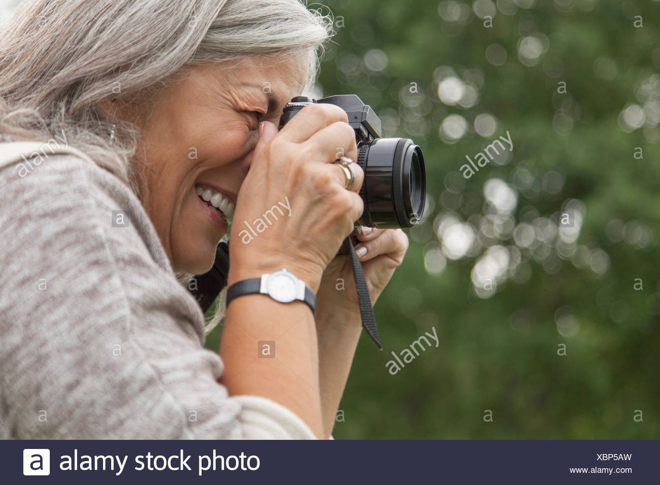 senior woman taking pictures outdoors - Stock Image