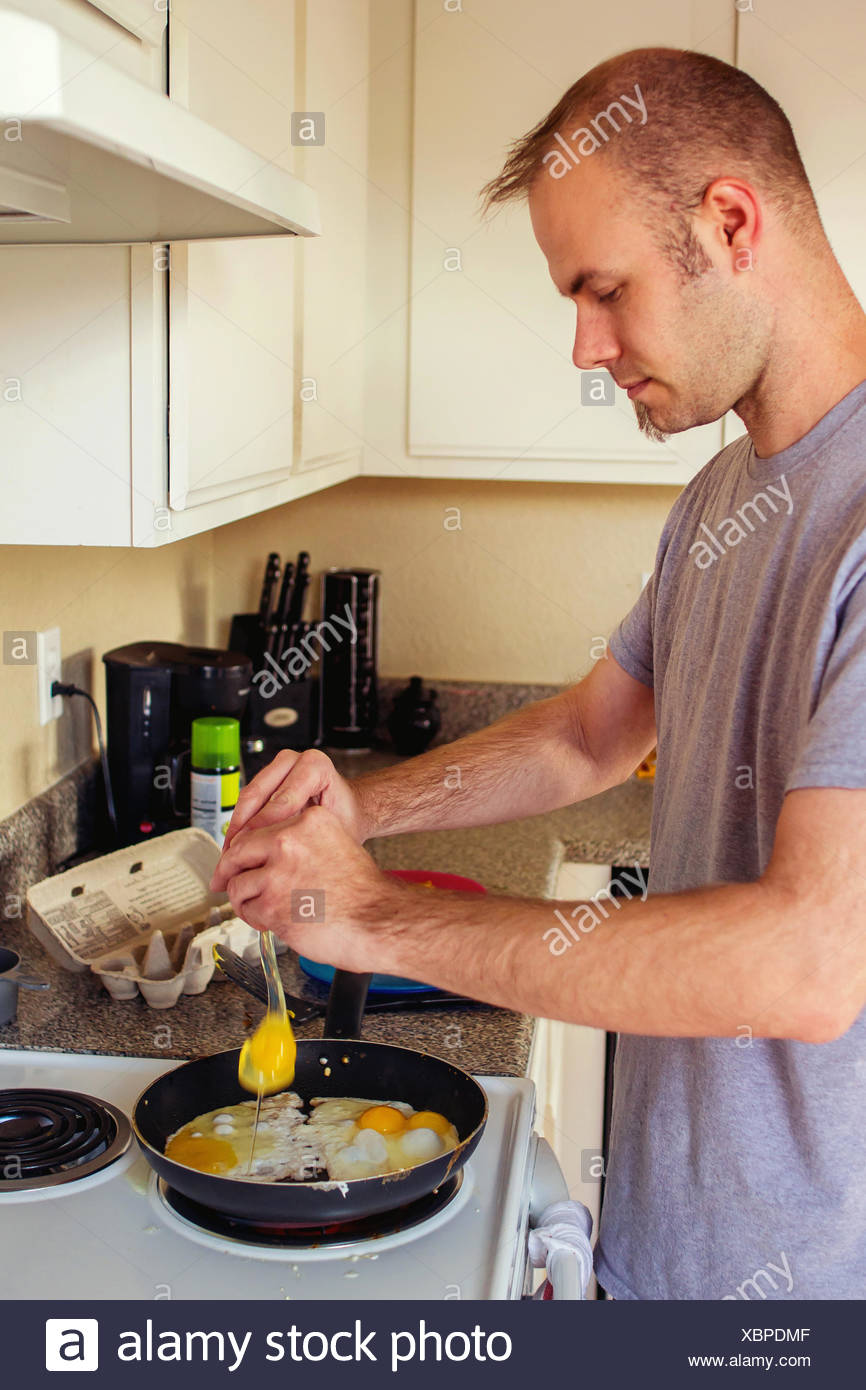 Man cooking fried eggs for breakfast - Stock Image