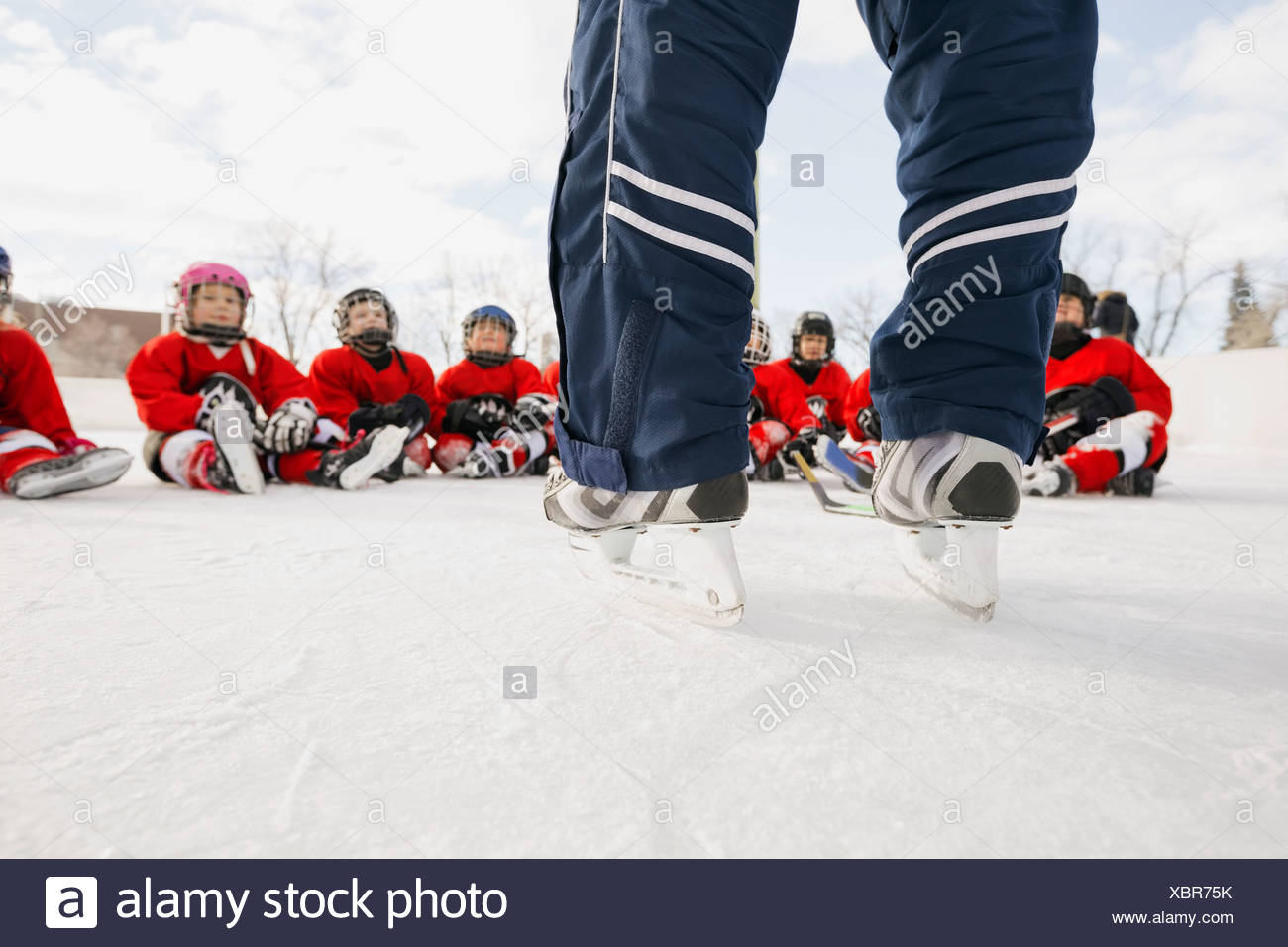 Low section of coach standing in front of ice hockey team - Stock Image