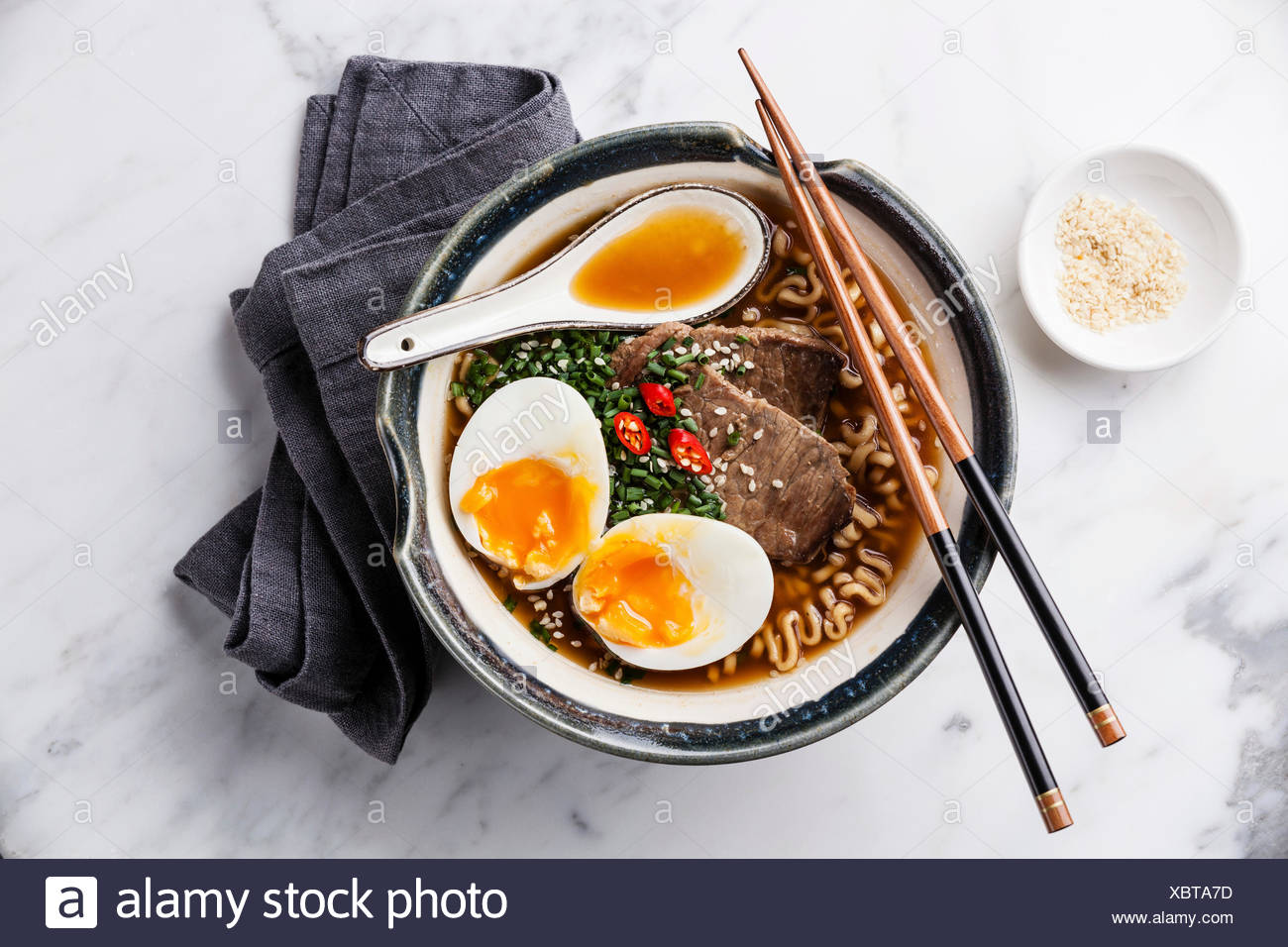 Miso Ramen Asian noodles with beef and egg in bowl on white marble background - Stock Image