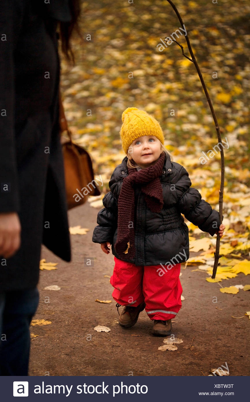 Young girl on walk wearing winter clothes, holding stick - Stock Image
