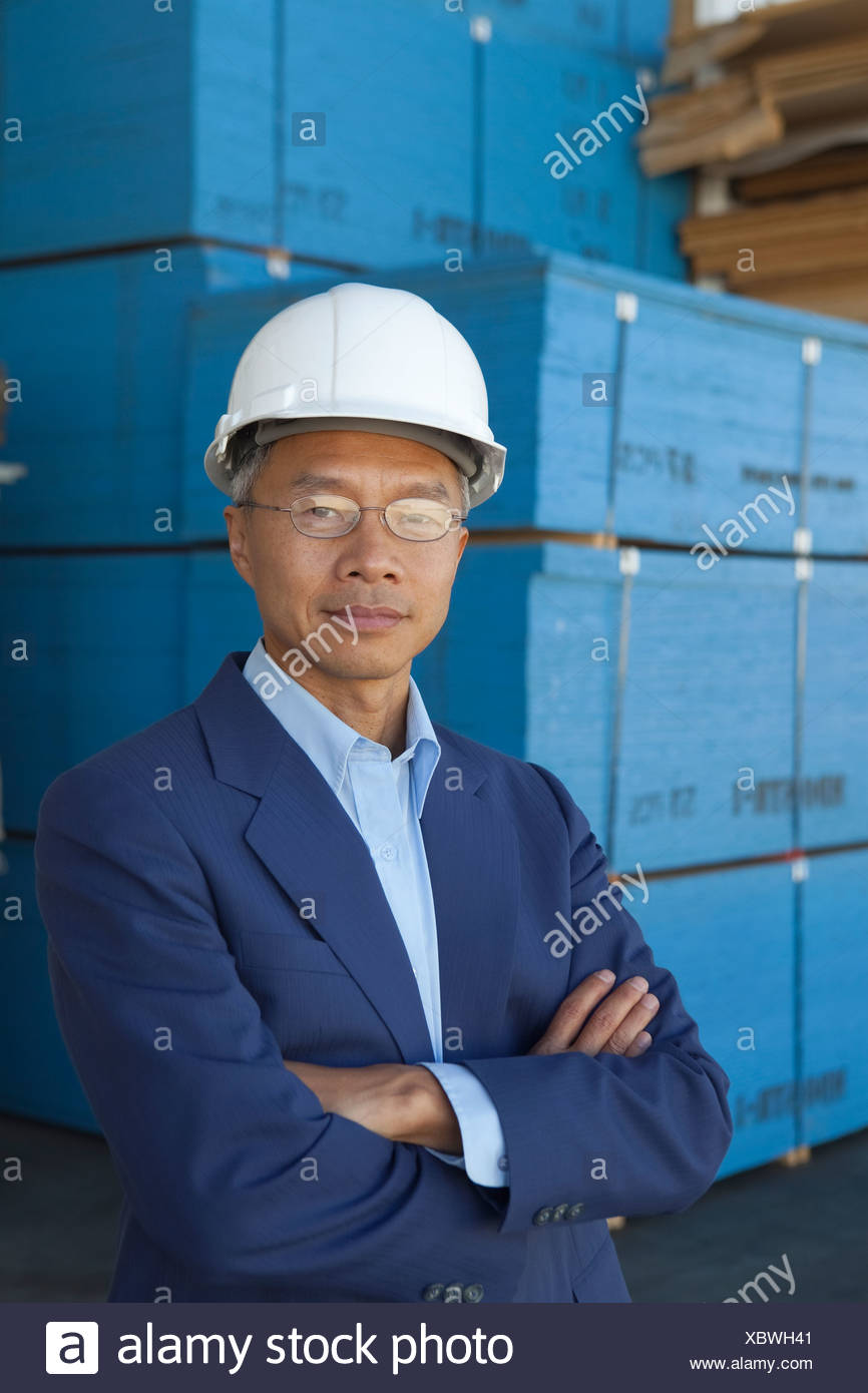 Portrait of manager wearing hard hat with arms crossed - Stock Image