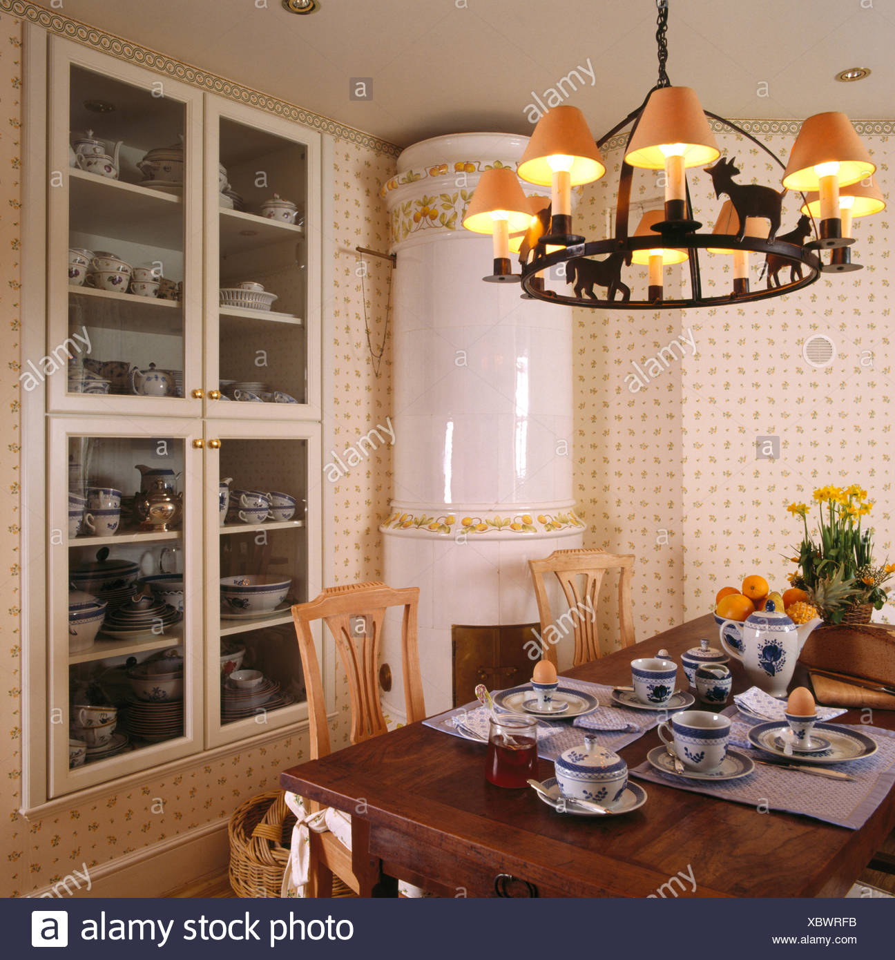 Shades On Wrought Iron Ceiling Light Above Table Set For Breakfast In Dining Room With Large White Ceramic Stove