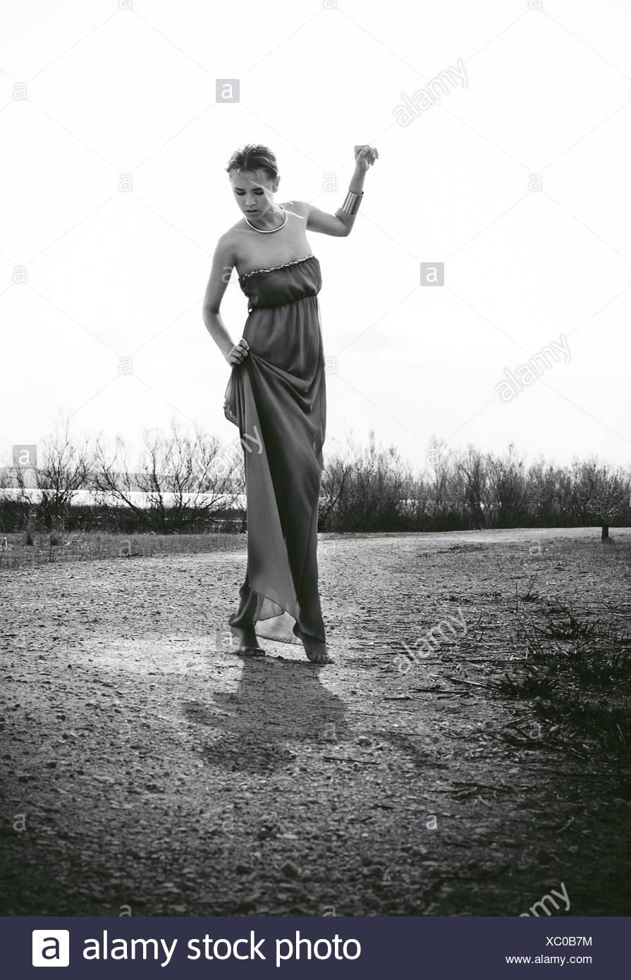 Woman wearing long dress standing in meadow - Stock Image