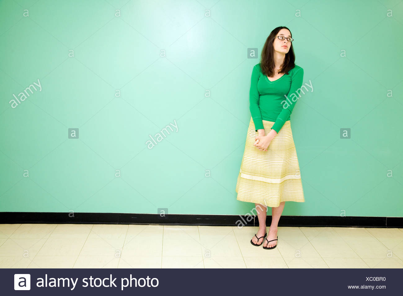 Young woman against a green wall - Stock Image