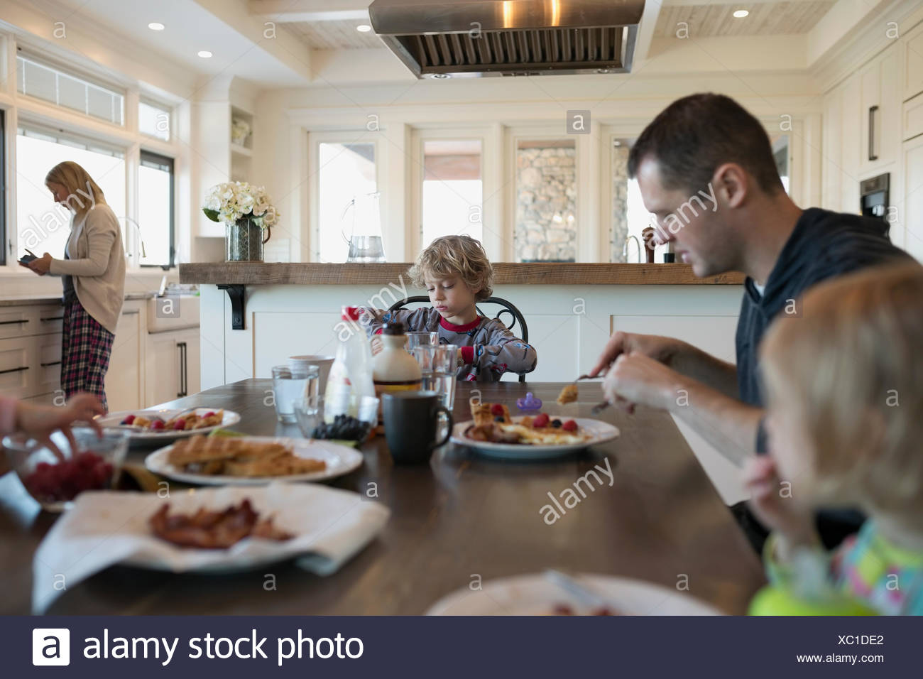Family eating waffles at breakfast table - Stock Image