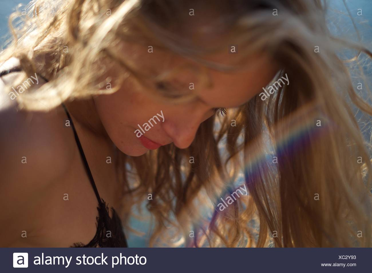 Woman looking down with beam of rainbow light - Stock Image
