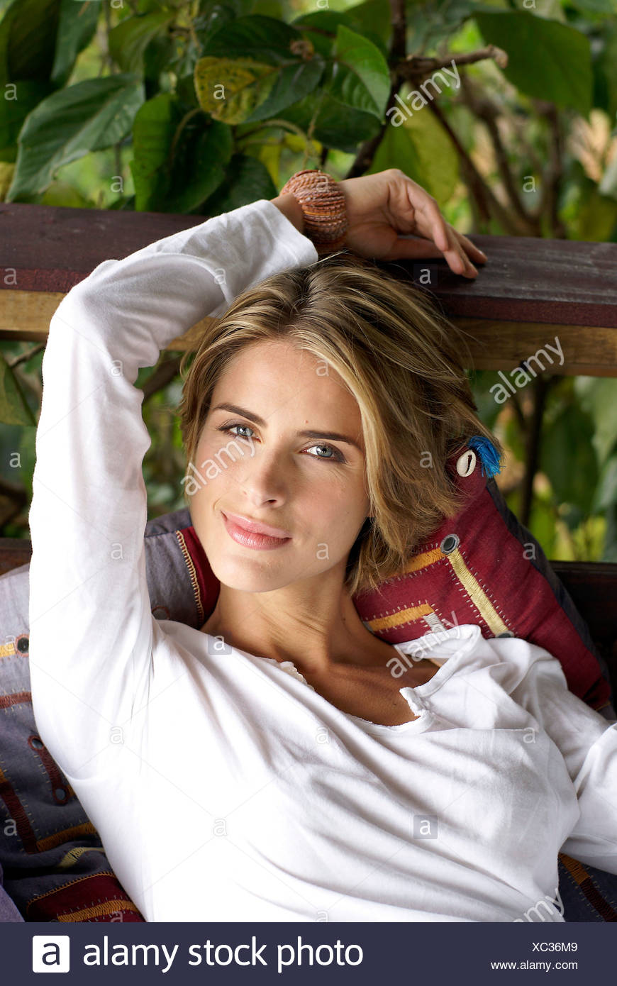 35a12412c3f3e Female with short dark blonde hair with highlights wearing white long  sleeve top sitting relaxed on cushions outdoors