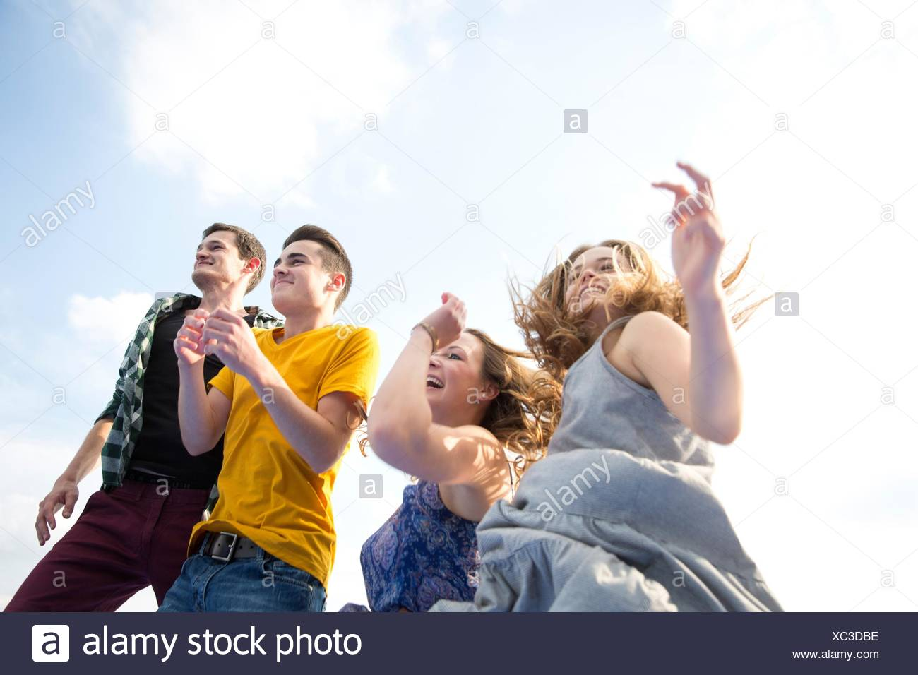 Group of young adults, running, outdoors, low angle view - Stock Image