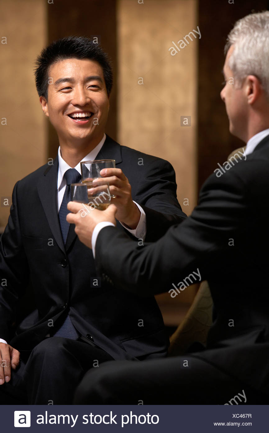 Two business leaders share a toast at an exclusive business club - Stock Image