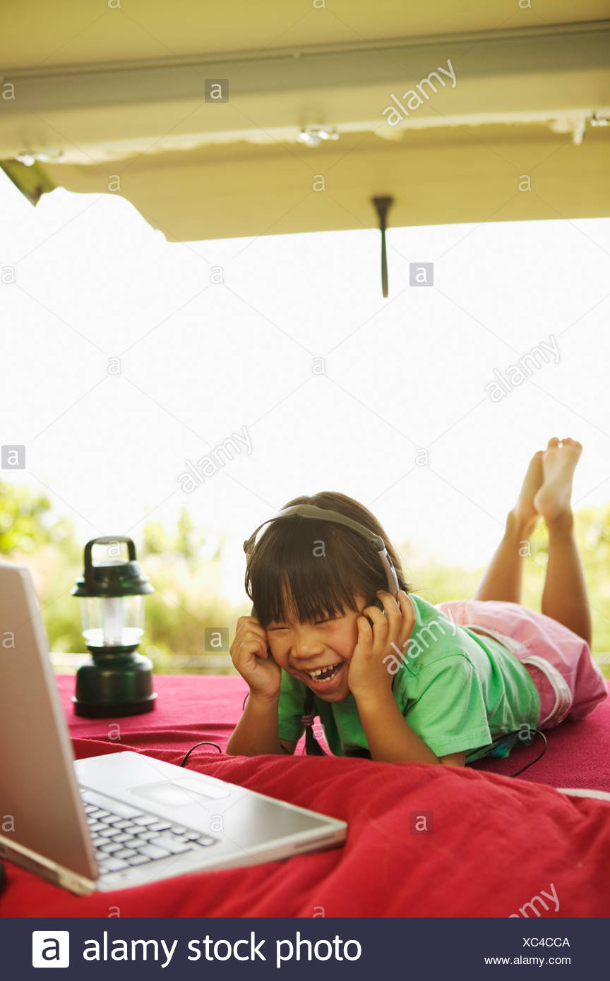 Girl using a laptop in the back of a minivan - Stock Image