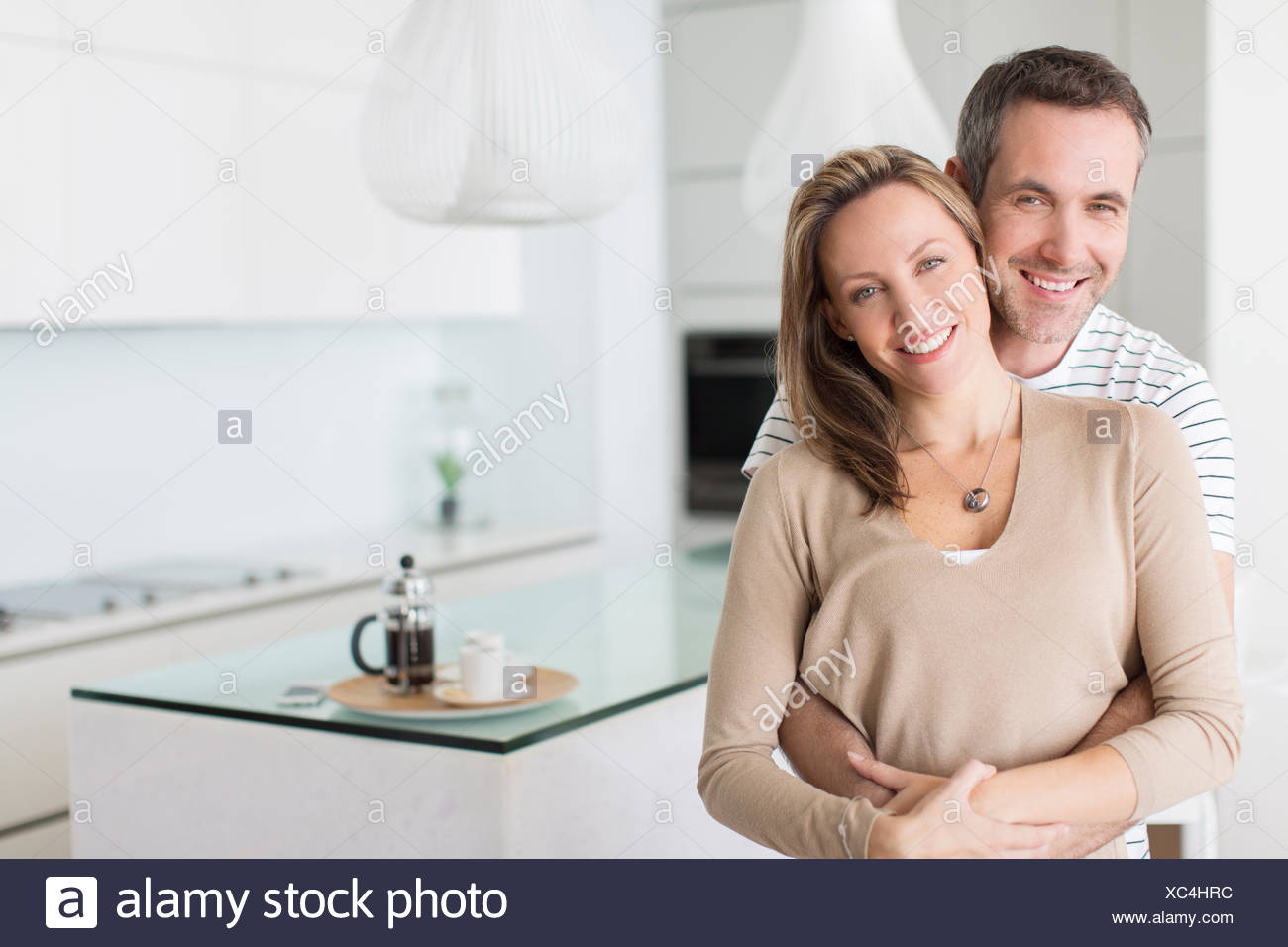 Couple hugging in modern kitchen - Stock Image