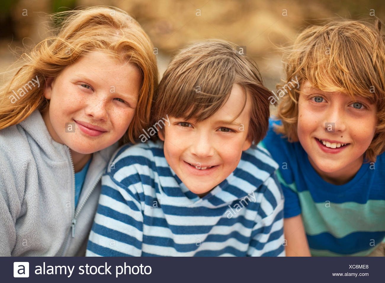 Portrait of three friends smiling at camera - Stock Image