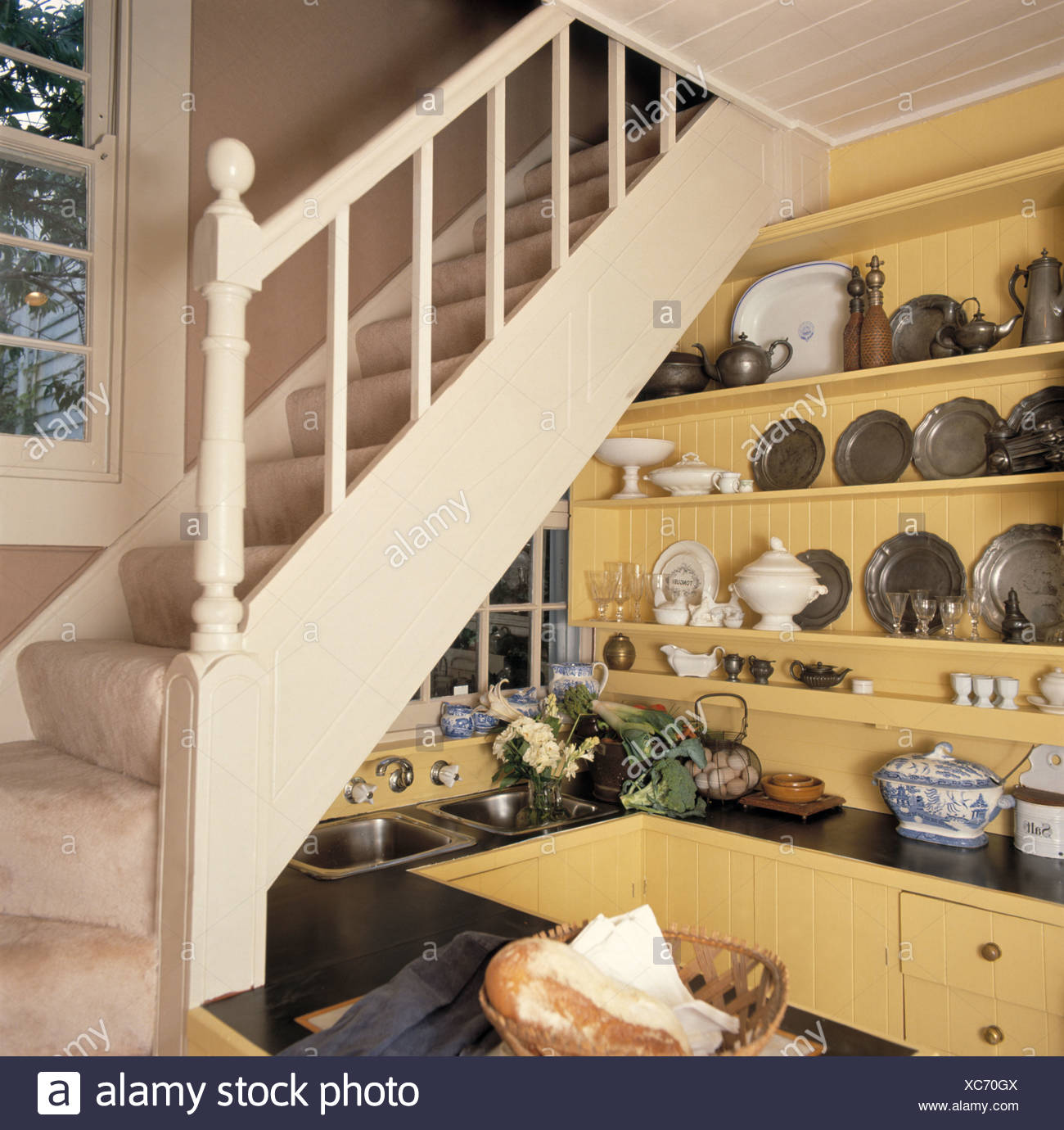 Pewter Plates On Shelves Of Small Yellow Kitchen Below Cream Staircase In  Traditional Hall
