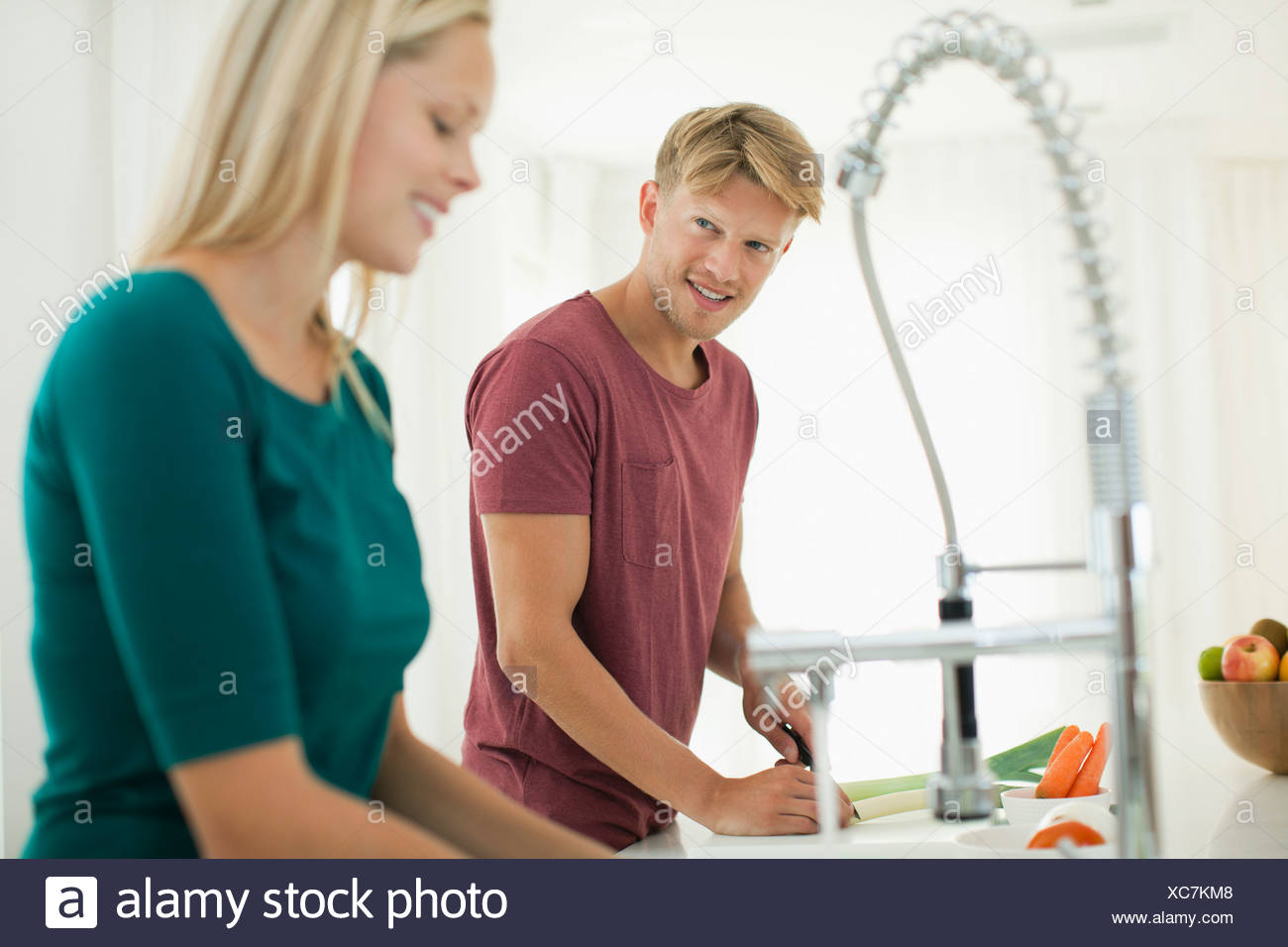 Couple working together in kitchen - Stock Image