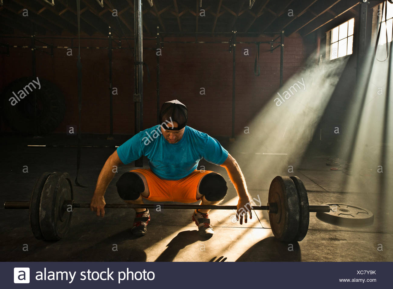 A male athlete prepares to deadlift. - Stock Image