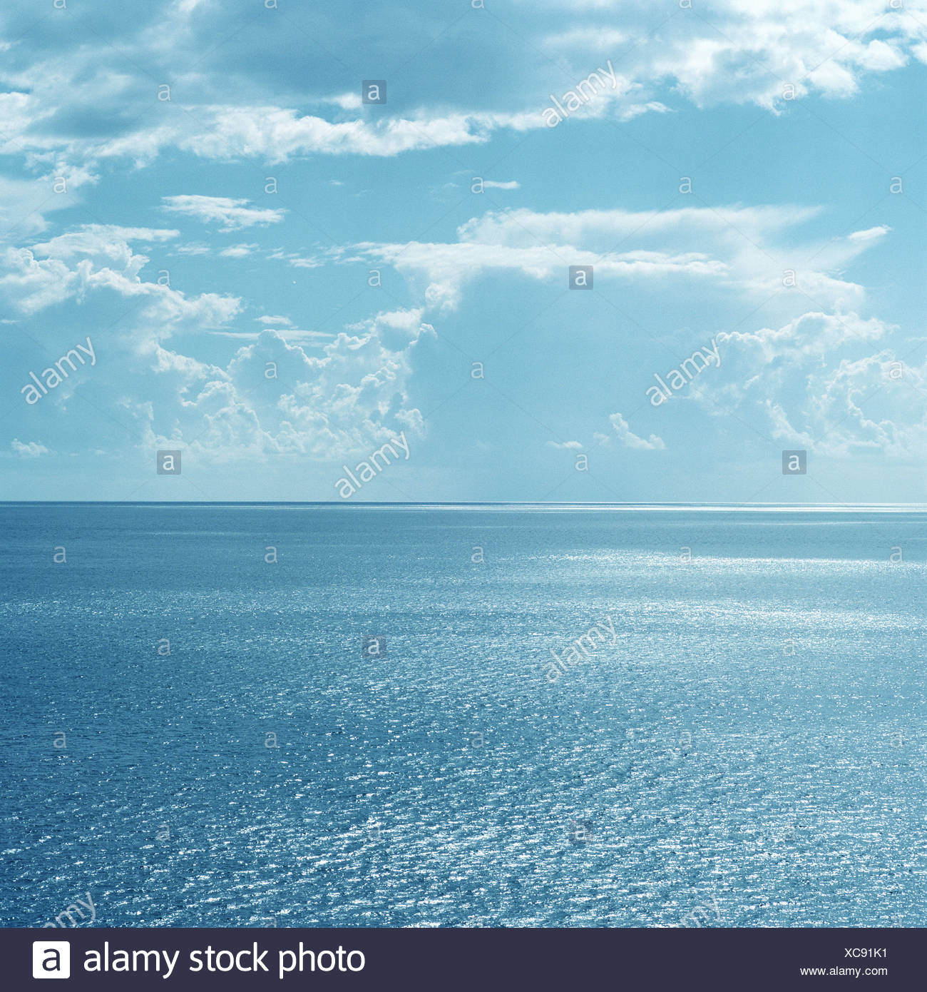Clouds over still ocean waters - Stock Image