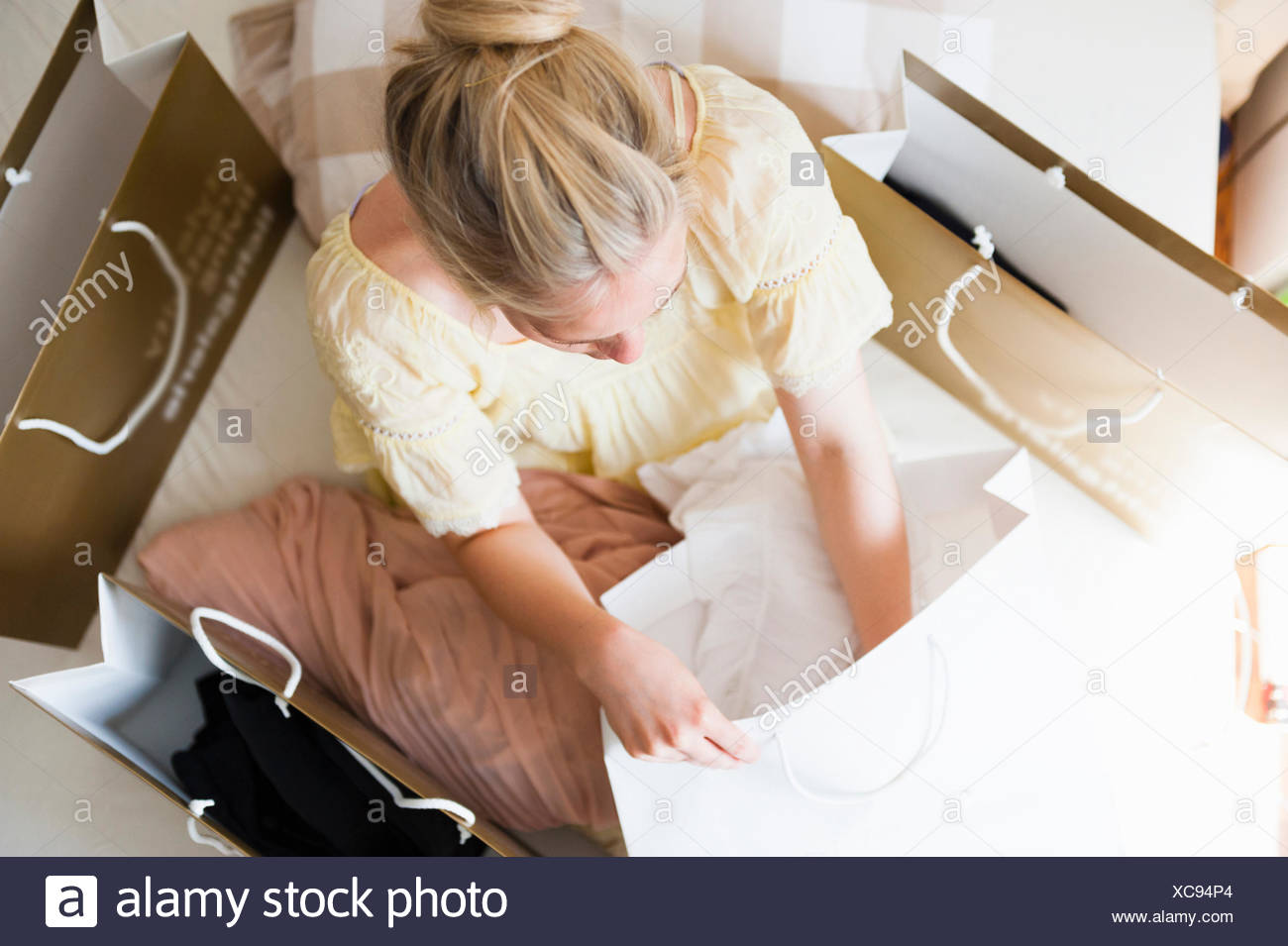 Overhead view of young woman on bed surrounded by shopping bags - Stock Image
