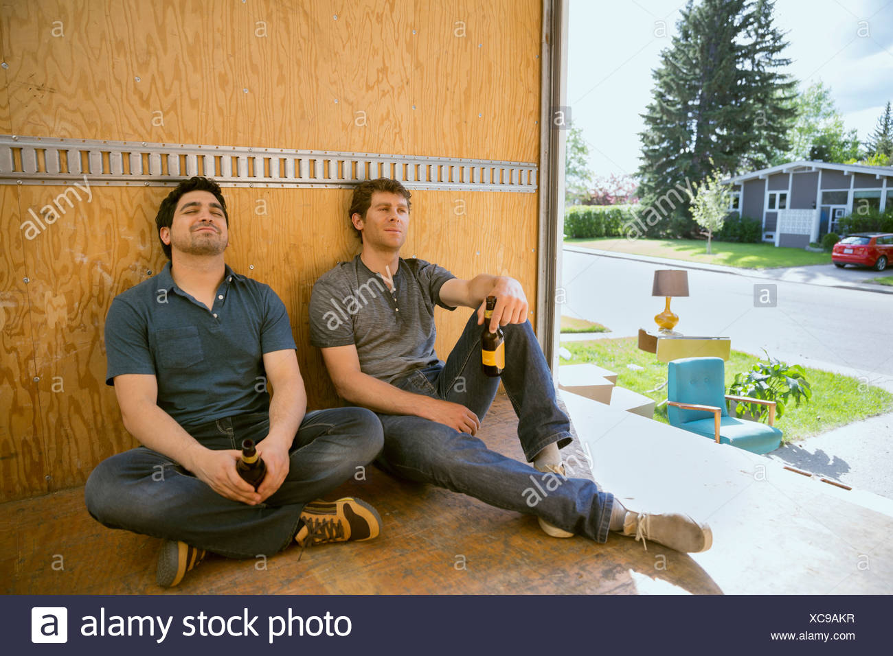 Men drinking beer and resting inside moving van - Stock Image