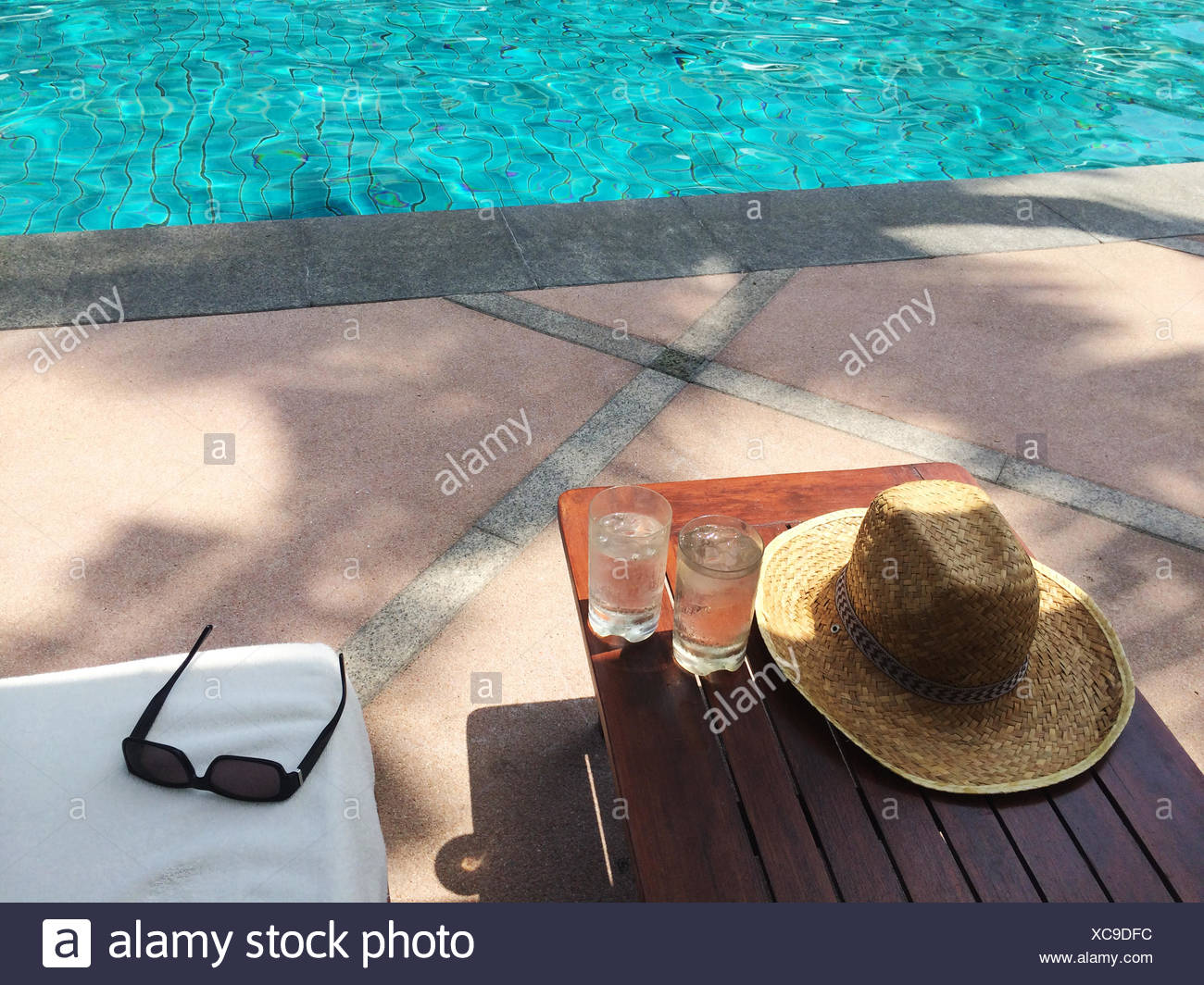 Straw sun hat, sunglasses and two glasses of water by swimming pool - Stock Image