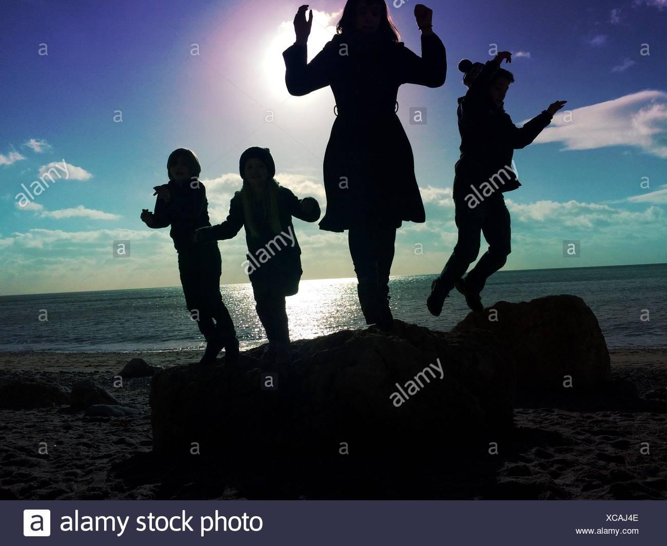People Enjoying At Beach Against Sky - Stock Image