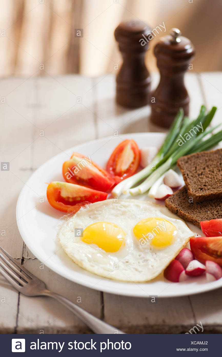 Two fried eggs with yellow yolks and vegetables - Stock Image