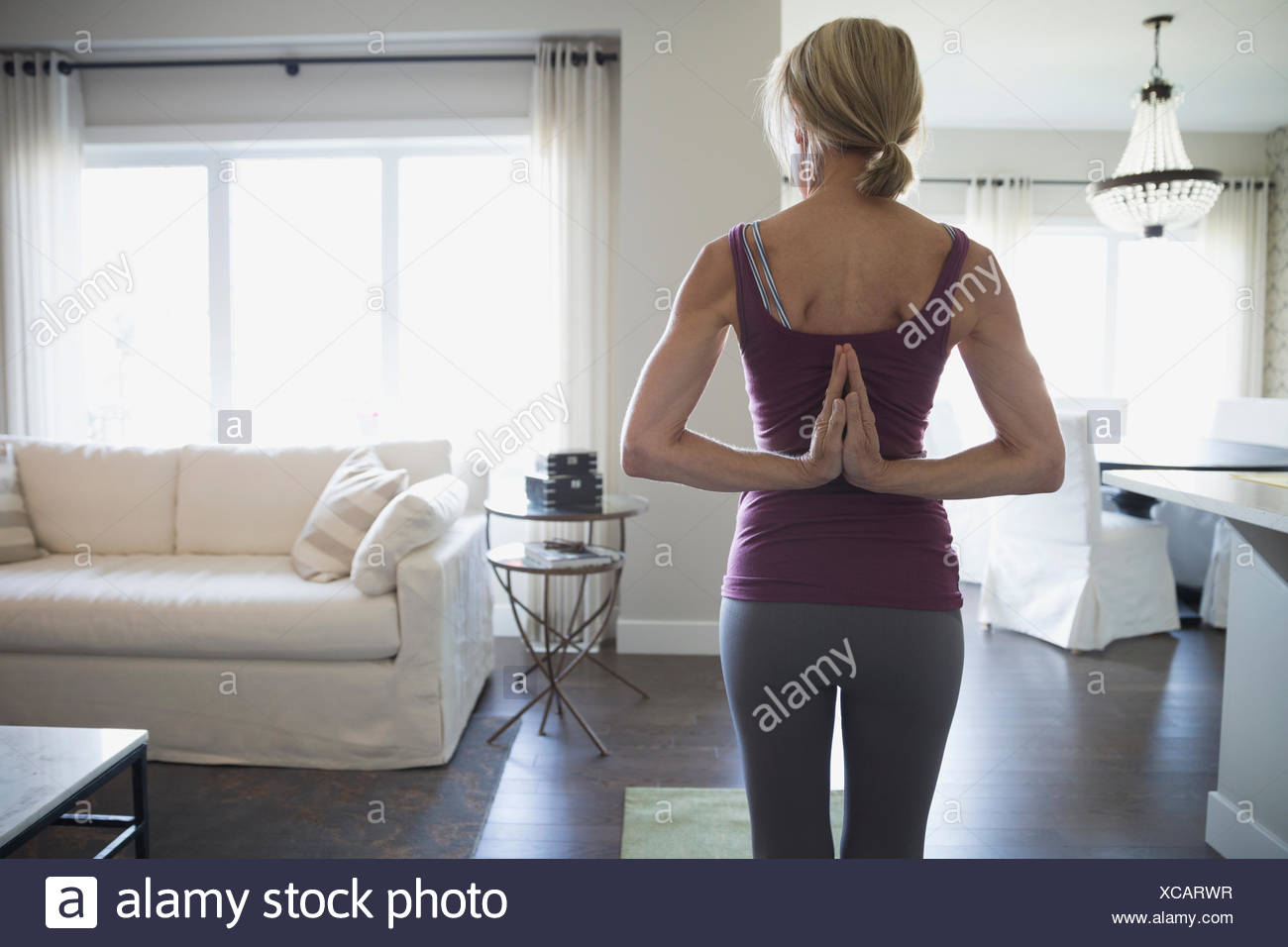 Senior woman practicing yoga with hands behind back - Stock Image