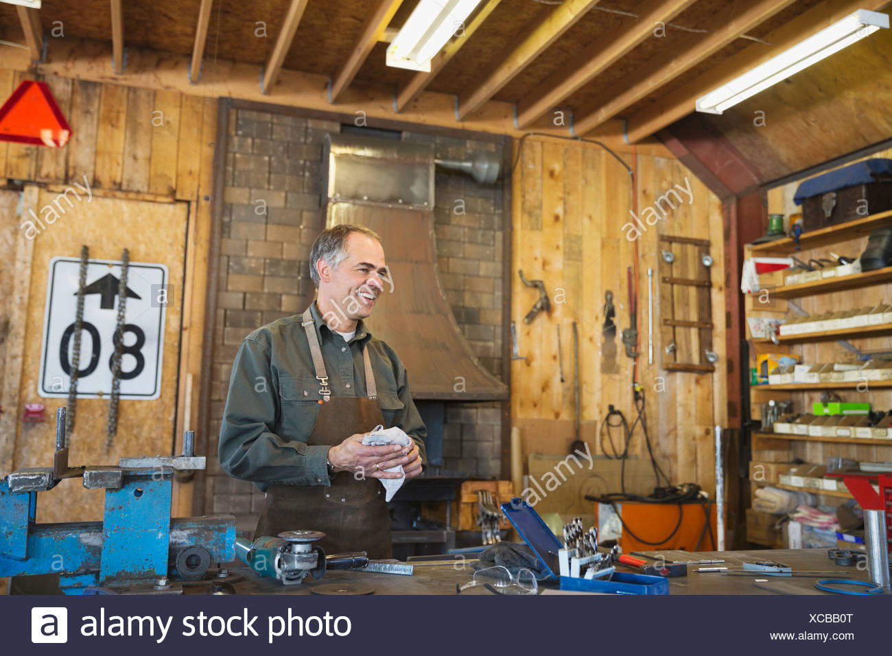Metalworker cleaning up at workbench - Stock Image