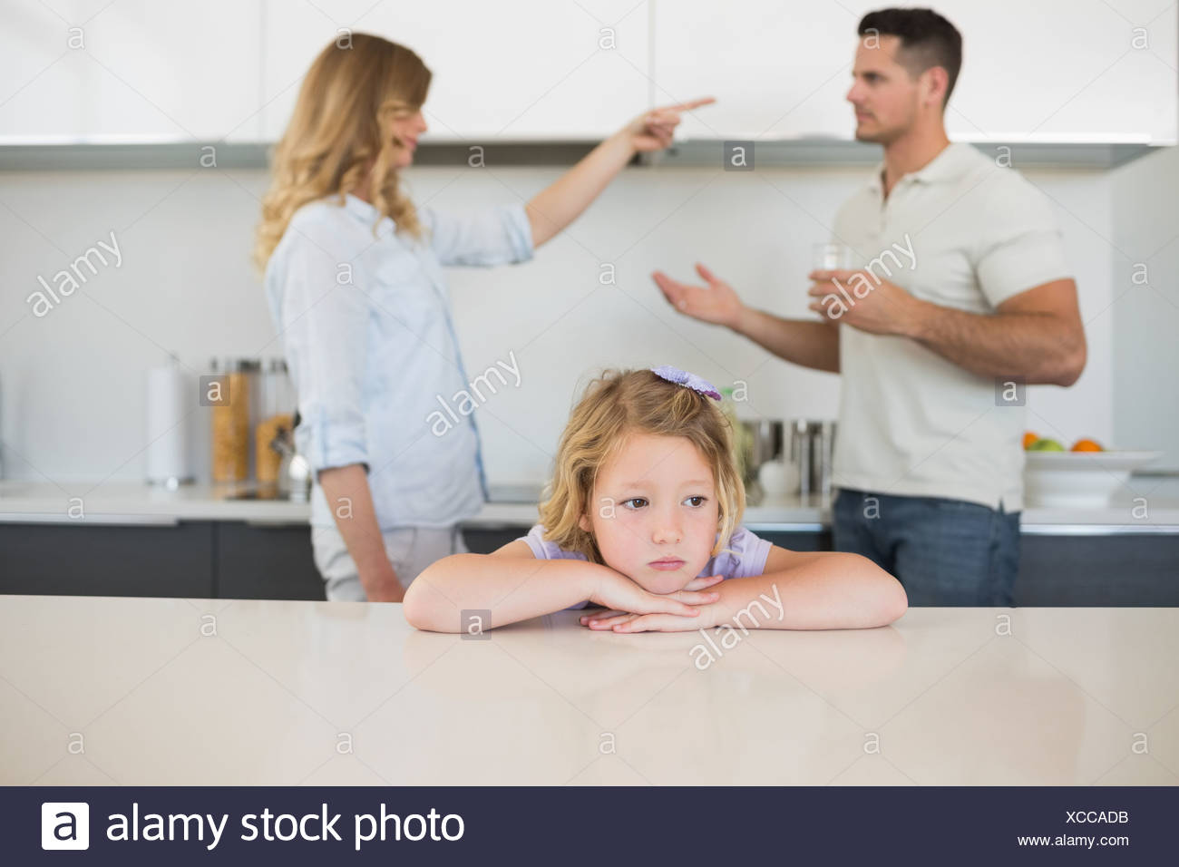 Sad girl against arguing parents - Stock Image